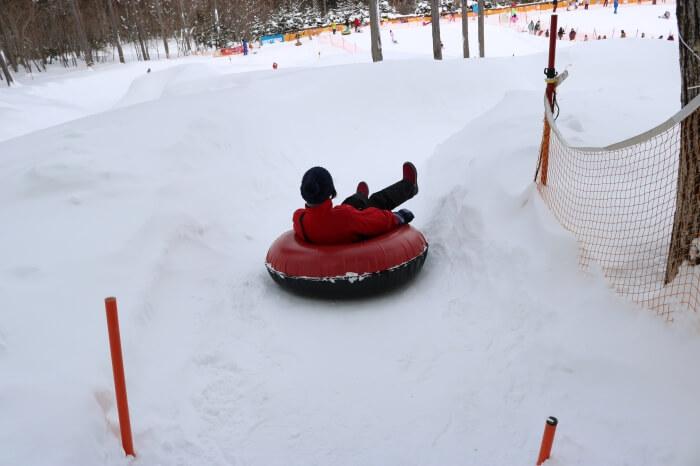 ハンターマウンテン塩原スキー場キッズパークのチュービングコースでチュービング遊びをするママ