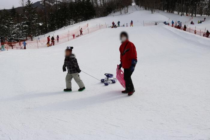 ハンターマウンテン塩原スキー場キッズパークのそり用ゲレンデでそり遊びをするママとみなちゃん