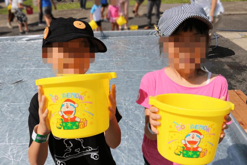 むさしの村の鮎のつかみ取り体験でバケツを持つ子供